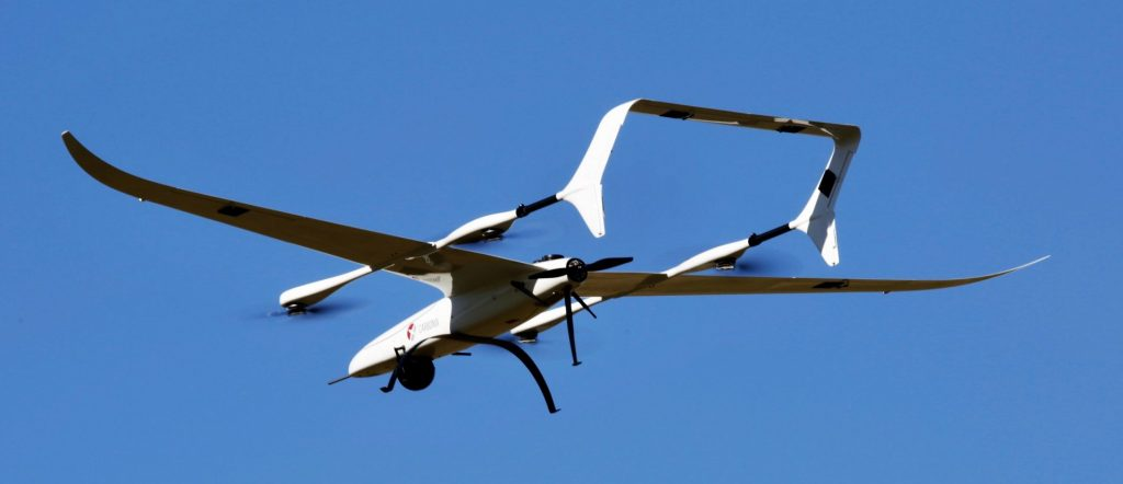 Carbonix Volanti shown hovering. The thin high-aspect wings are organically curved and flex precisely under aerodynamic loads.